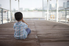 Alone little boy sitting at the pier Stock Photos