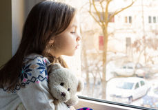 Alone little girl at the window Stock Photography