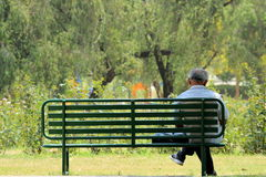 Alone and loneliness. Depressed and sad old man on bench in park or garden ,from back angle Stock Photos