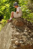 Alone and Lost. Boy alone sitting on a large boulder Royalty Free Stock Photography