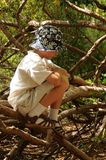 Alone and Lost. Boy alone sitting on a bunch of branches Stock Photo