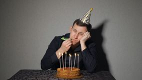 Alone man celebrates a holiday, he sits alone at a table with a cake and a candles.  stock video