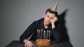 Alone man celebrates a holiday, he sits alone at a table with a cake and a candles.  royalty free stock images
