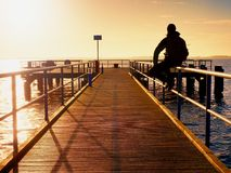 Alone man goes on the wooden pier in the sunrise Stock Photo