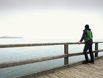Alone man at handrail, autumn misty morning on sea pier. Depressive. Alone man at handrail, autumn misty morning on sea pier. Depression, dark atmosphere stock photos