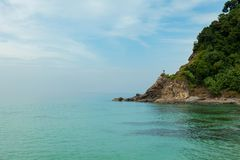 Alone man holding thumbs up standing on stone at tropical sea in. Summer season beautiful scenery landscape view in thailand Stock Photography