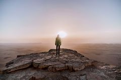Alone man in israel negev desert admires the view of sunrise. Young male person stands on the edge of the cliff royalty free stock photo