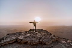 Alone man in israel negev desert admires the view of sunrise. Young male person stands on the edge of the cliff. Of makhtesh ramon park. Beautiful horizon Stock Photos