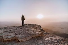 Alone man in israel negev desert admires the view of sunrise. Young male person stands on the edge of the cliff. Of makhtesh ramon park. Beautiful horizon Royalty Free Stock Images