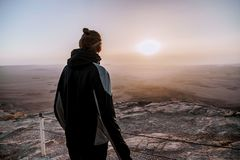Alone man in israel negev desert admires the view of sunrise. Young male person stands on the edge of the cliff. Of makhtesh ramon park. Beautiful horizon Royalty Free Stock Image