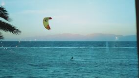 Alone man kite surfing in red sea at sunset, Dahab Egypt, point of view from window. People windsurfing and kite surfing