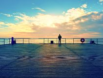 Alone man on pier and look over handrail into water. Sunny sky, smooth water level. Vivid and strong vignetting effect stock photos