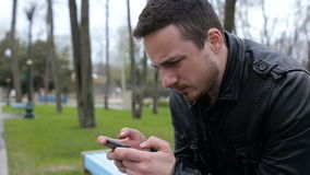 Alone man playing on phone in the park. Young man playing touch screen phone in the park stock video footage