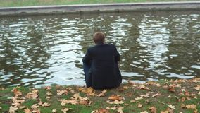 Alone Man Sits On The Bank. Slow motion shot of a man in suit sits on the bank of the canal in autumn day stock video