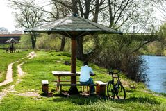 Alone man is sitting on bench and bicycle in park by the river on spring day stock photo