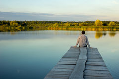 Alone man sitting on the edge of a pier. On the lake Stock Photo