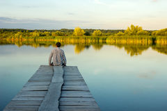 Alone man sitting on the edge of a pier stock images