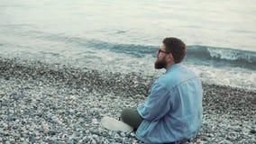 Alone man is sitting on ground of gravel beach near sea, resting ,turning around stock video