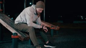 Alone man is sitting on sport equipment in park at night and using smartwatch. Sportsman is resting after training in park at night, adjusting smartwatch. He is stock video footage