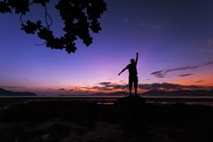 Alone man tourist standing on the stone in tropical sea and enjoying scenery during sunrise or sunset beautiful light dramatic sky royalty free stock image