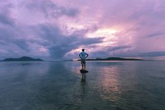 Alone man tourist standing on the stone in tropical sea and enjoying scenery during sunrise or sunset beautiful light dramatic sky stock photography