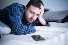 Man addicted to smartphone portrait in bed stock photos