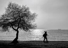 Alone man walking on the beach. A man walking alone in deserted beach Royalty Free Stock Photo