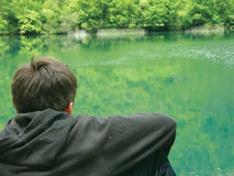 Alone meditate boy and river. View at a alone boy on the river in deep mind. Teenager in black clothes sits near the green river and thinking - deep in mind Stock Photography