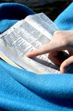 Alone with my Bible. Young woman points to a verse in her Bible.  She is wrapped in a bright blue blanket Stock Photos