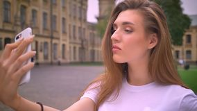 Alone nice caucasian girl standing close-up near camera and taking selfie with focused face in urban background.  stock video footage