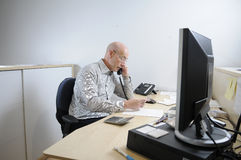 Alone at the office. A bald man sitting in an office and talking on the phone Royalty Free Stock Image