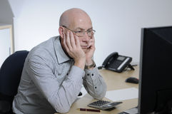 Alone at the office. A bald man sitting in an office Royalty Free Stock Images