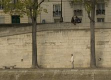 Alone in Paris. A couple and a man alone by the Seine in Paris, France Royalty Free Stock Photo