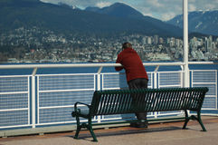 Alone at the park. A man standing by a bench Royalty Free Stock Photography