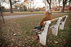 Alone in the Park. An old man sitting on a bench outside by himself. The image orientation is horizontal and there is copy space royalty free stock image
