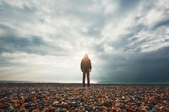 Alone and pensive. Silhouette of the alone and pensive man on the beach stock photography