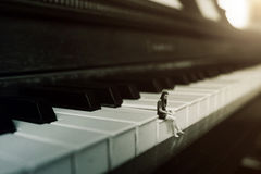 Alone on the piano. A woman sitting on a piano all alone stock photography