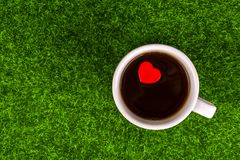 Alone red heart. Shape in coffee cup on grass Stock Image