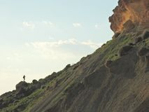 Lone Person on Rocky Ridge Summit. Lone person on a rocky ridge looking up towards the top of the ridge Stock Photo