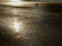 Alone in the sand. Couple walking along the beach at low tide royalty free stock photos