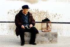 Alone senior man and birdcage Stock Photo
