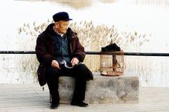 Alone senior man and birdcage Stock Photo