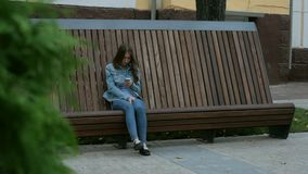 Alone serious Girl sitting on the bench and texting with mobile phone in jeans. Alone Female serious Girl sitting on the wooden bench and texting flip through stock video footage