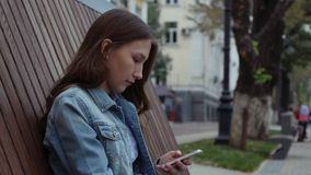 Alone serious Girl sitting on the bench and texting with mobile phone in jeans. Alone Female serious Girl sitting on the wooden bench and texting flip through stock footage