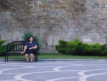 Alone sitting woman on a bench Stock Photography