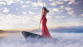Alone smart woman paddling in the clouds. Alone smart lady paddling in the clouds stock photos