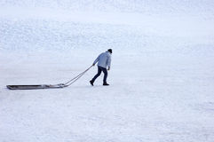 Alone in the snow. A solitary man drags a sledge across a wide open expanse of snow Royalty Free Stock Photos