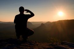 Alone sportsman in black. Tall hiker in squatting position enjoy view at sunset on mountain peak Royalty Free Stock Photos