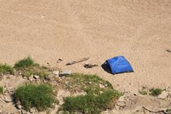Lonely tent on the beach. Alone standing blue tent placed on the edge of a sandy beach and vegetation Royalty Free Stock Photos