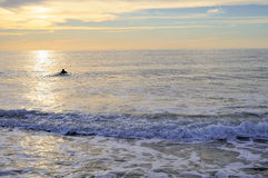 Alone surfer in the sunset Stock Photo